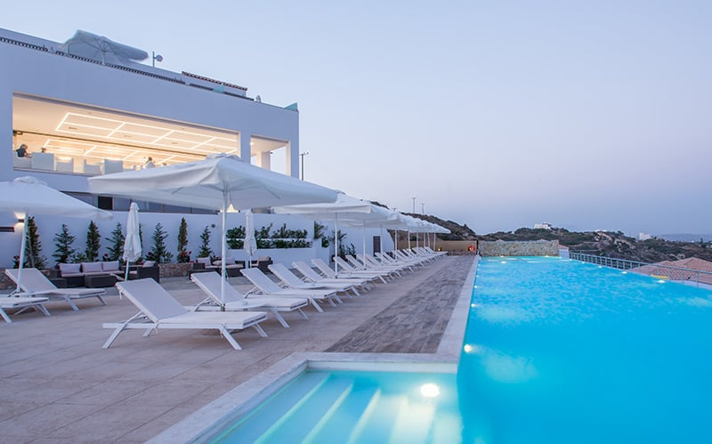 Sun loungers and umbrellas by the infinity pool in 5 star hotel in Kos.