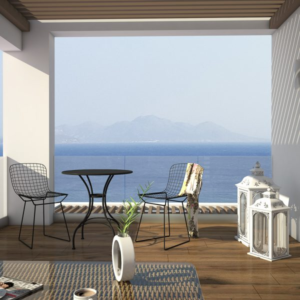 Two modern chairs and a round table at the private balcony overlooking the sea.