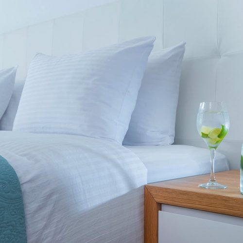 Bottle and glass with lemon juice next to the double bed of Junior Suite Sea.