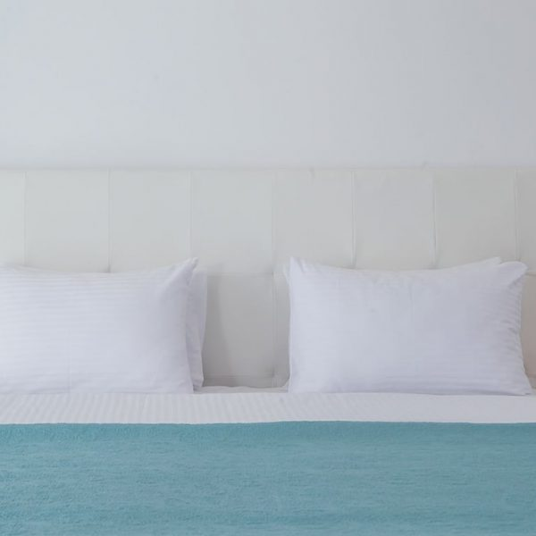 King size double bed covered with a blue blanket in Junior Suite Sea at White Rock of Kos.