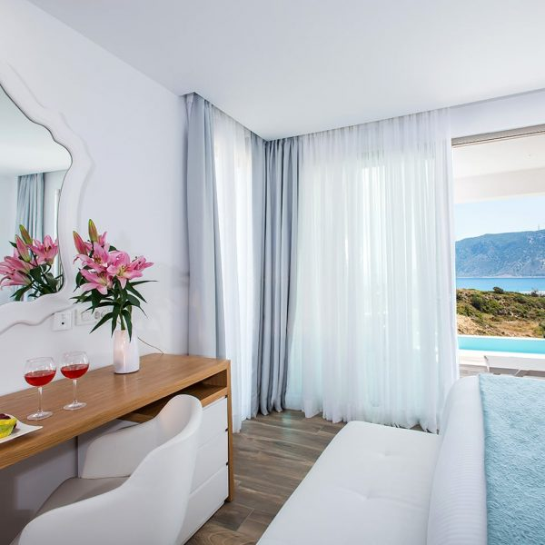 Desk with white chair and a mirror in Pool Experience Junior Suite with sea view.