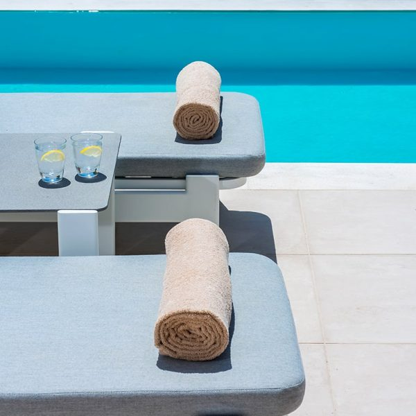 Towels on sun loungers near the pool in Pool Experience Junior Suite with sea view.