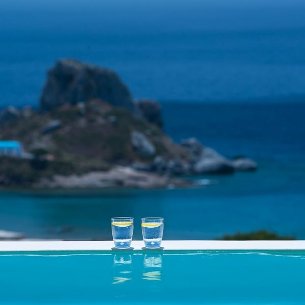 Two glasses of water by the edge of the pool overlooking the sea in White Rock of Kos.