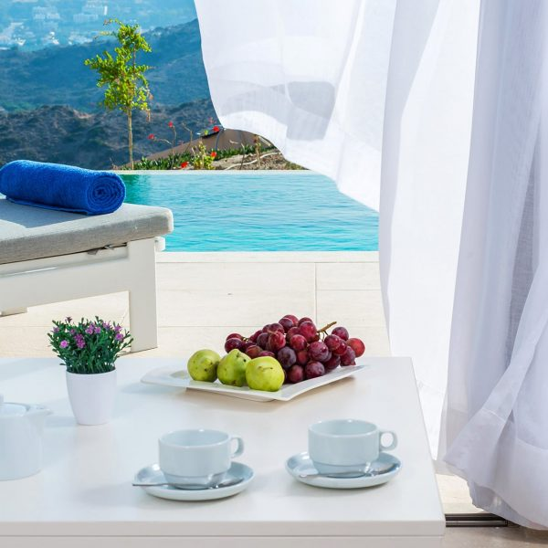 The breakfast is served on a table near the pool with amazing view.