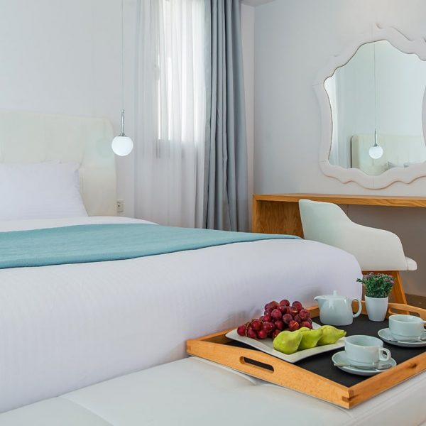 King size bed, white sofa and a tray with fruit and coffee at Junior Suite Sea.