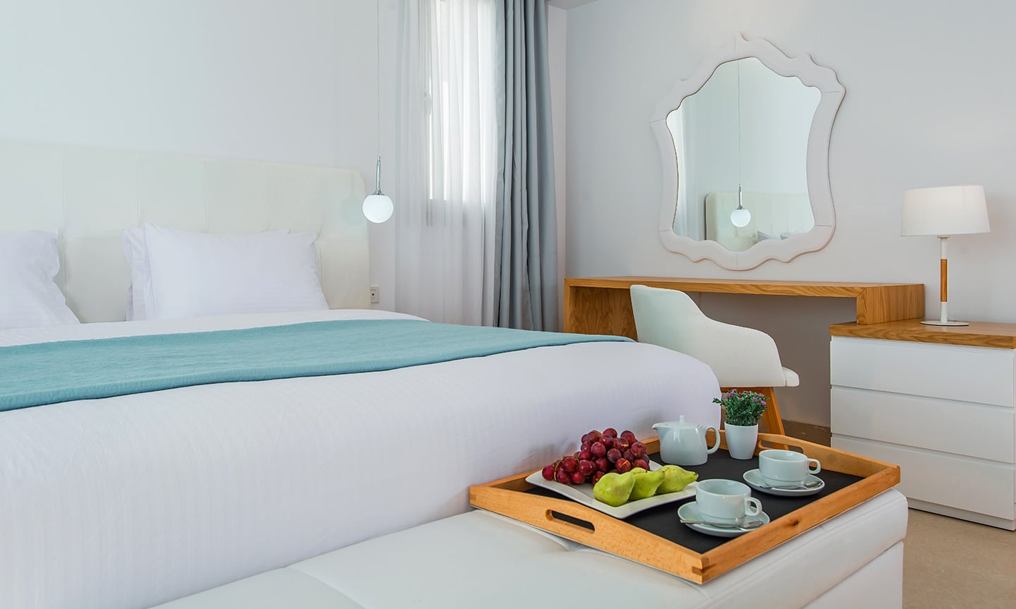 A comfortable king size bed and a tray with coffee and fruits by the bed in White Rock of Kos.